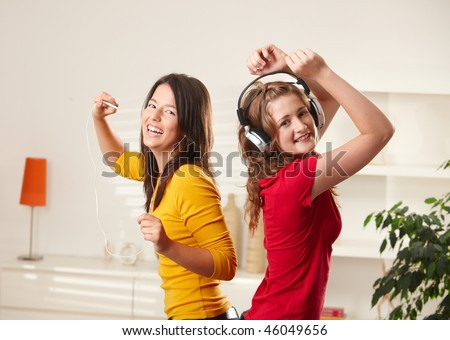 stock photo happy teen girls listening to music via headphone and earphone having fun together at home dancing 46049656 stock photo : sister and brother on sledge, winter friendship