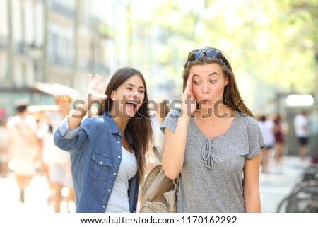 Happy teen greeting waving hand and friend ignoring her in the street