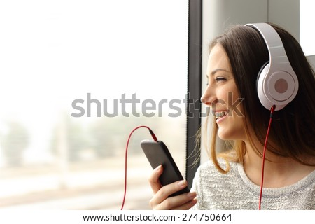Happy teen passenger listening to the music traveling in a train and looking through the window #274750664