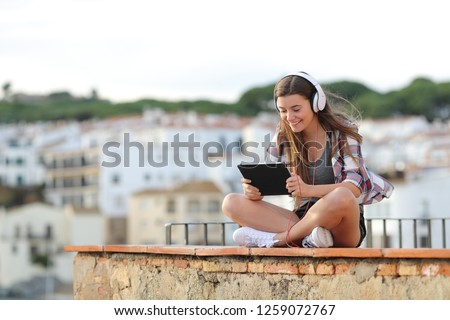 Happy teen wearing headphones watching and listening online video on a tablet sitting on a ledge on vacation #1259072767