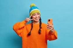 Happy teenage Asian girl with two pigtails dressed in warm knitted orange sweater and winter hat makes peace gesture and takes selfie portrait via mobile phone poses against blue background.