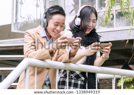 Happy teenage boy and teenage girl in headphones listening to music from smartphone and play video games outdoor. Technology concept