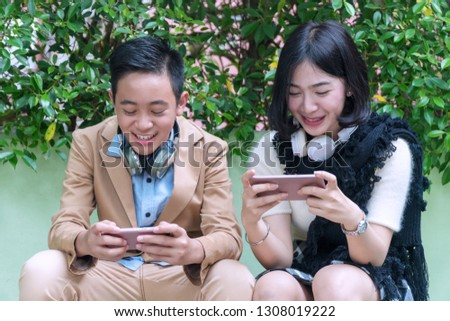 Happy teenage boy and teenage girl sitting on chair with headphones play video games online from smartphone in the garden. Technology concept