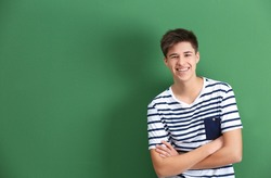 Happy teenage boy in casual clothes on color background