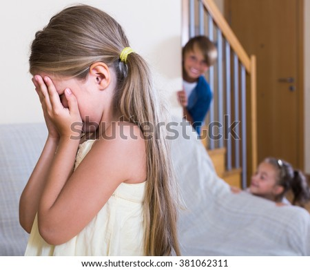 happy teenage boy with little sisters playing hide-and-go-seek