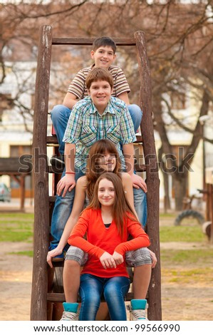 Happy teenage boys and girls spending time together in the park on sunny spring day.