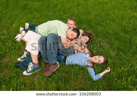 Happy teenage friends having fun in the grass.