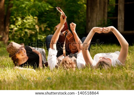 Happy teenage friends relax with guitar music on the green meadow