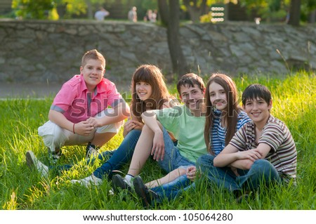 Happy teenage friends spending time together in the park on sunny summer day.
