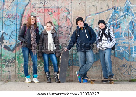 Happy teenage friends with school bags and skateboards standing in front of the graffiti wall.
