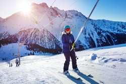 Happy teenage girl lifting on the ski drag lift rope in bright sport outfit and smiling with last sunset light