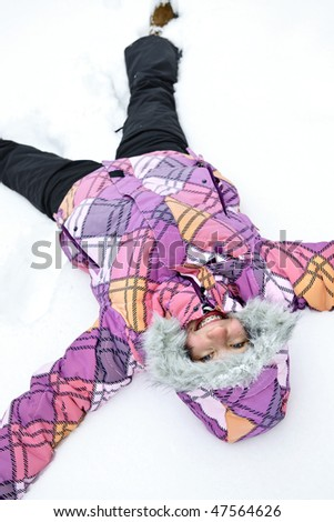 Happy teenage girl making snow angel in winter