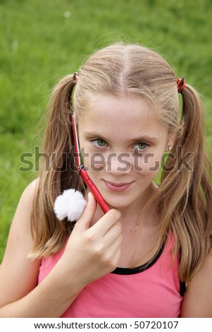 Happy teenage girl talks on cellular phone on green grass background