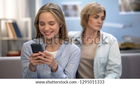 Happy teenage girl texting messages in smartphone, sad mother sitting on sofa