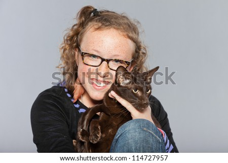 Happy teenage girl with glasses and blond curly hair hugging dark brown eastern shorthair cat. Studio shot isolated on grey background.