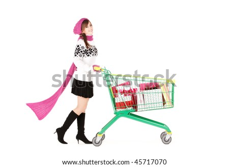 happy teenage girl with shopping cart over white