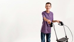 Happy teenaged disabled boy with cerebral palsy smiling at camera, taking steps with his walker isolated over white background. Children with disabilities and special needs concept. Web Banner