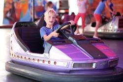 Happy teenager boy rides electric car during fan-fair entertainment