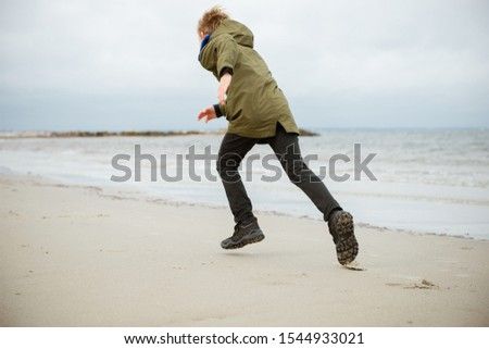 Happy teenager boy running on water of Baltic sea in rubber boots at cold and windy weather