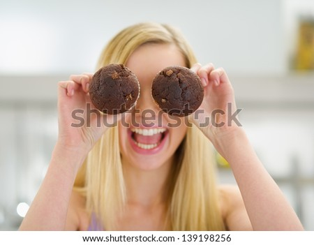 Happy teenager girl holding chocolate muffins in front of face