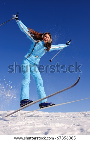 happy teenager girl jumping with skies