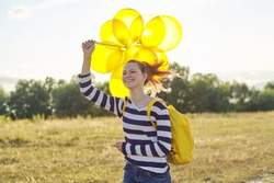 Happy teenager girl with yellow balloons and backpack running and jumping along country road in summer meadow. Freedom, life, joy, holiday concept