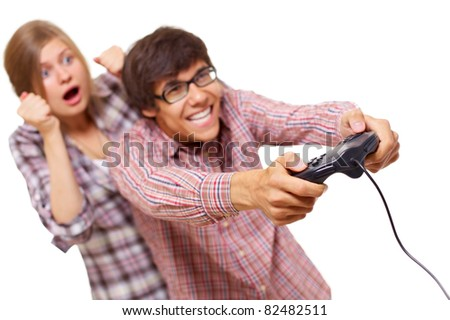 Happy teenager in checked shirt and black glasses playing video game with passion and his girlfriend supports him. Focus on joystick, mask included