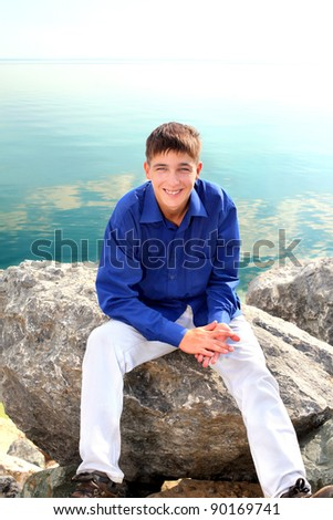 happy teenager sitting near the water
