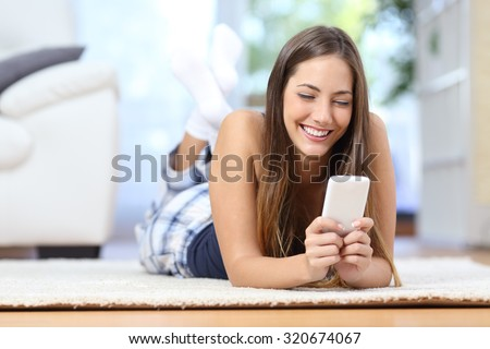 Happy teenager texting on the mobile phone lying on a carpet in the living room