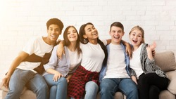 Happy teenagers embracing, sitting on sofa and smiling together to camera over light wall