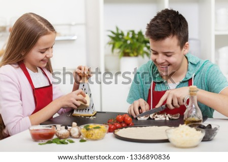 Happy teenagers having fun in the kitchen preparing a pizza and chatting with broad smiles on their faces