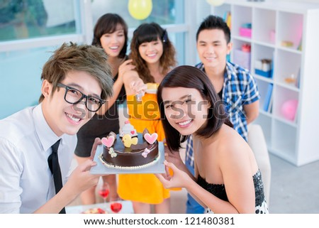Happy teenagers showing their birthday cake