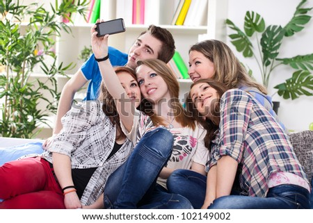 Happy teenagers taking group photo with smartphone
