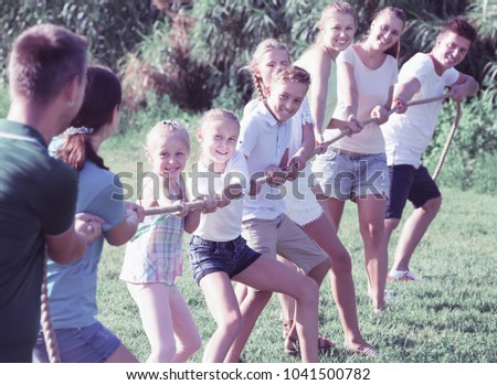 Happy Teenagers With Parents Playing Active Games In Summer Park Tugging War 1041500782