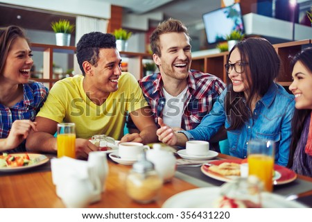 Happy teens talking during lunch in cafe