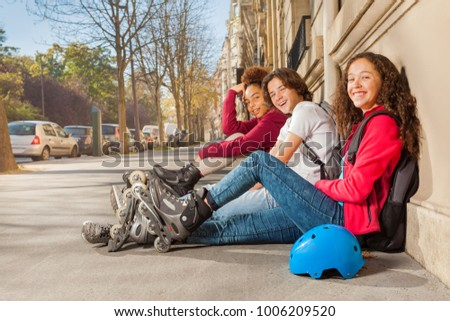 Happy teens with rollerblades sitting at sidewalk
