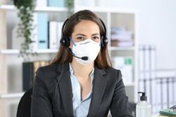 Happy telemarketer woman posing looking at camera avoiding covid-19 with mask sitting at the office