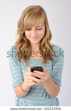 Happy Texting. Thirteen year old girl smiling as she reads a text message on her smartphone. Note: Not Isolated.