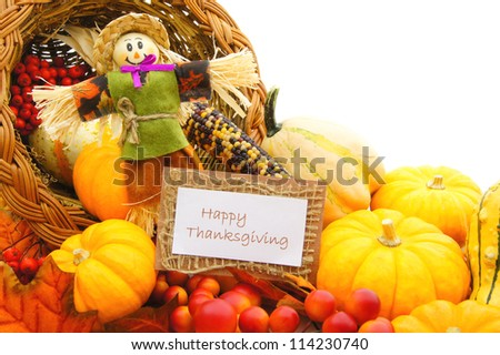 Happy Thanksgiving card and scarecrow among a cornucopia of autumn vegetables