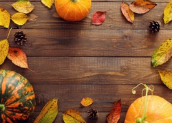 Happy Thanksgiving concept. Autumn frame with ripe orange pumpkins, fallen leaves, dry flowers on rustic wooden table. Flat lay, top view, copy space.