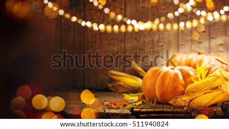 Happy Thanksgiving Day background, wooden table decorated with Pumpkins, Corncob, Candles and autumn leaves garland. Beautiful Holiday Autumn festival concept scene Fall, Harvest.