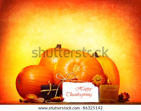 Happy thanksgiving day greeting card with traditional pumpkin and candles, holiday table setting