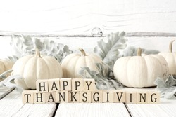 Happy Thanksgiving greeting on wooden blocks against a white wood background with white pumpkins and autumn leaves