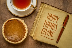 Happy Thanksgiving - handwriting in a retro, leather-bound journal with a pumpkin pie and a cup of tea, fall holiday greetings