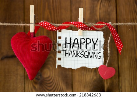 Happy thanksgiving message written on a paper hanging on the clothesline on wooden background with two hearts