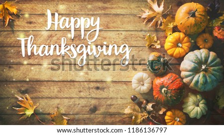 Happy Thanksgiving. Pumpkins with fruits and falling leaves on rustic wooden table - Shutterstock ID 1186136797