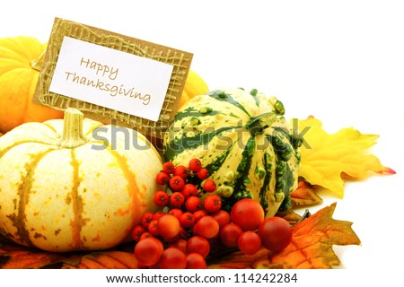 Happy Thanksgiving tag among a group of pumpkins, gourds and autumn leaves