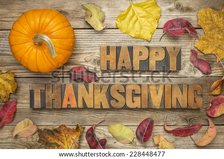 Happy Thanksgiving  - text in vintage letterpress wood type blocks against rustic wood background with a pumpkin and dry leaves