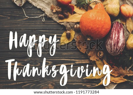 Happy Thanksgiving Text on beautiful composition of Pumpkin, autumn vegetables with colorful leaves,acorns,nuts, berries on wooden rustic table. Seasons greeting card #1191773284