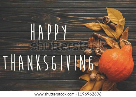 Happy Thanksgiving Text on beautiful Pumpkin with bright autumn leaves, acorns, nuts on wooden rustic table, flat lay. Seasons greeting card. Atmospheric image #1196962696
